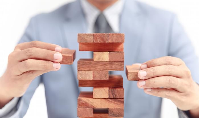 businessman building tower of wooden blocks