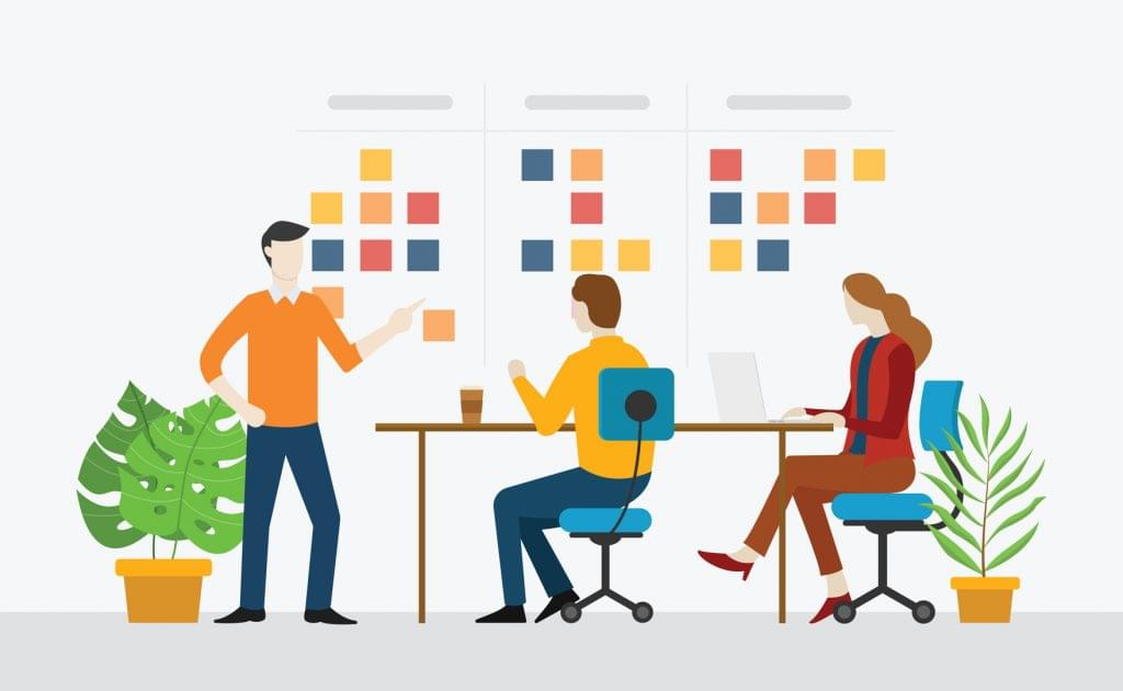 An agile team works together with Kanban sticky notes on a white board