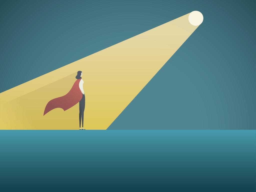 Businesswoman wearing a cape standing in a spotlight