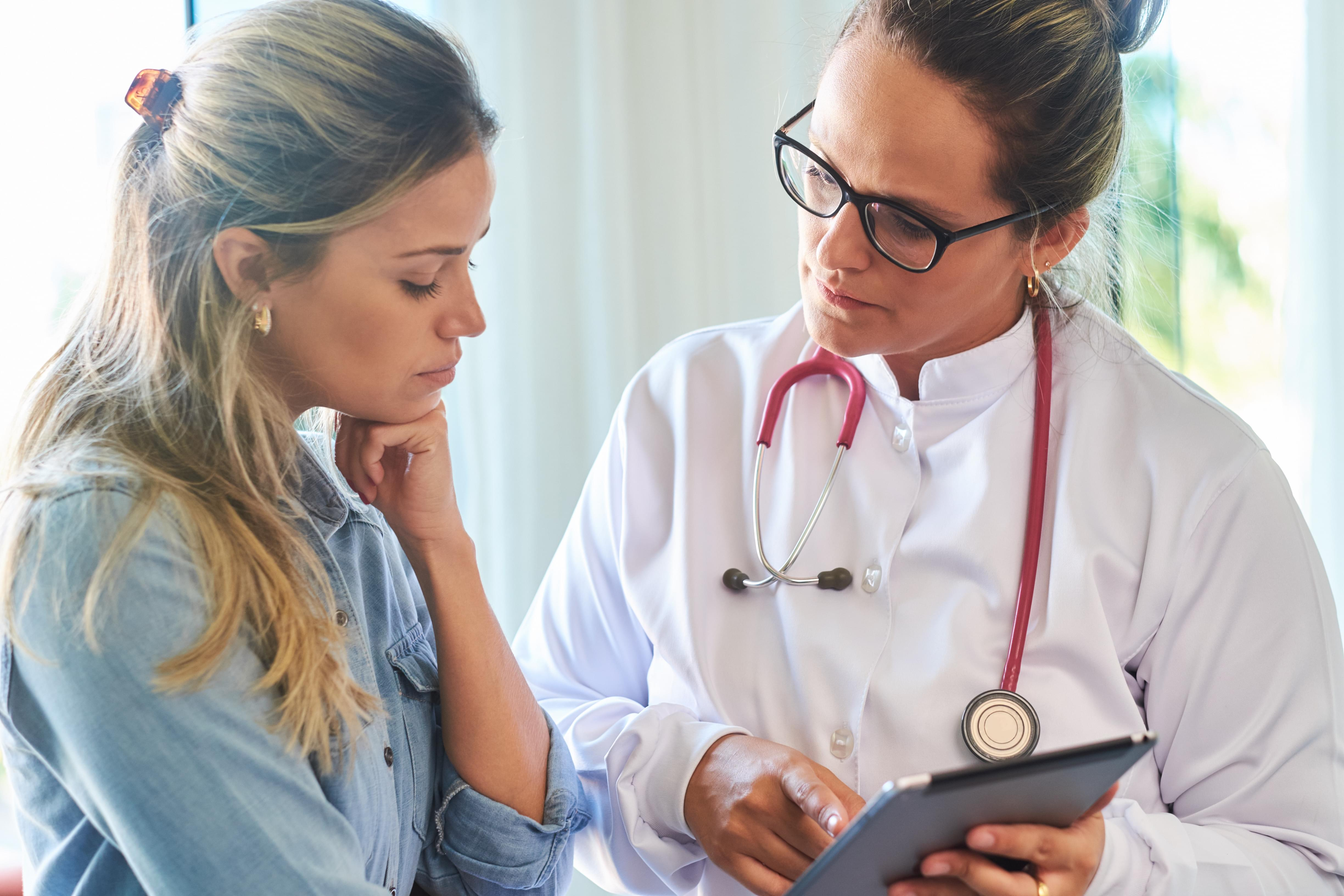 A doctor goes through a patient's health record on a tablet.