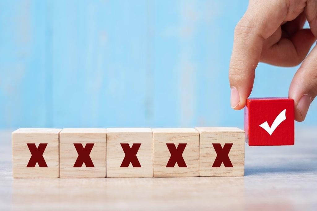 Person picking up one wooden block with a checkmark out of five others with Xs.