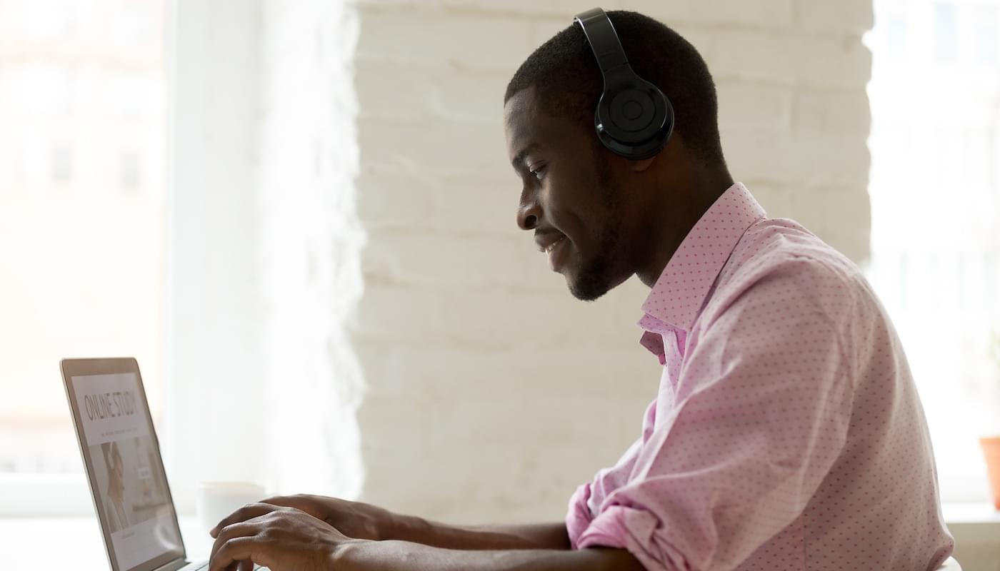 A student wearing headphones taking an online course.