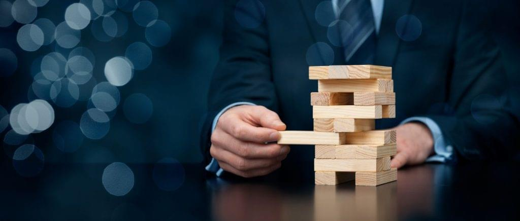 Businessman playing jenga game for gamification of training.