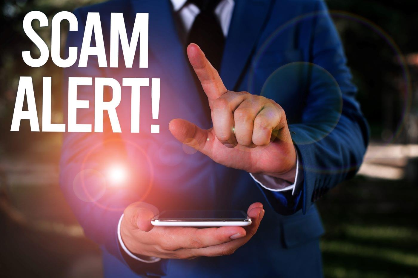 "Person holding their cellphone with the caption ""Scam Alert"" to denote a smishing attack"