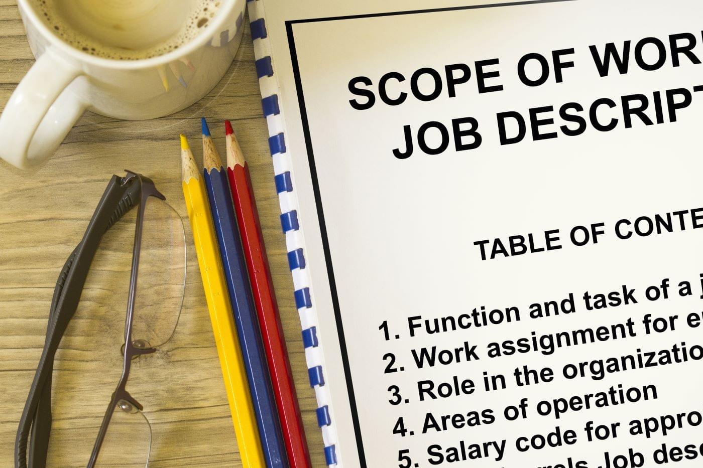 Pencils, glasses, coffee, and a notebook describing job descriptions