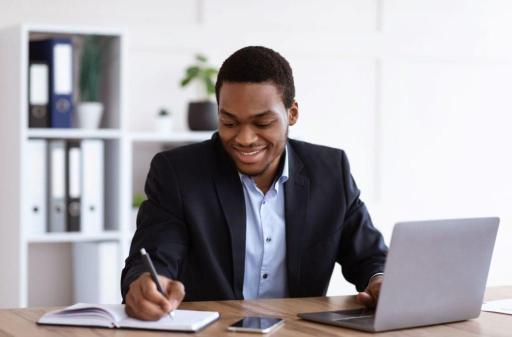 Millennial man taking notes at a laptop with a cellphone on the desk.