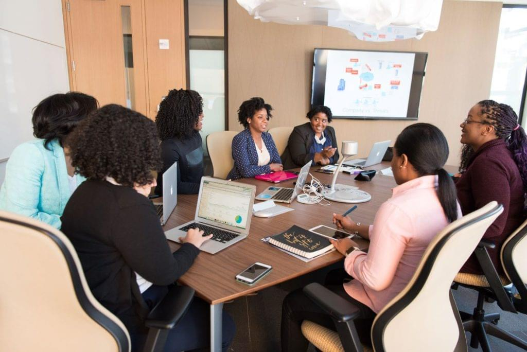 Businesswomen meeting around a conference table discussing business growth.