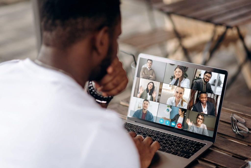 Man getting to know his team through web conferencing software during remote onboarding.