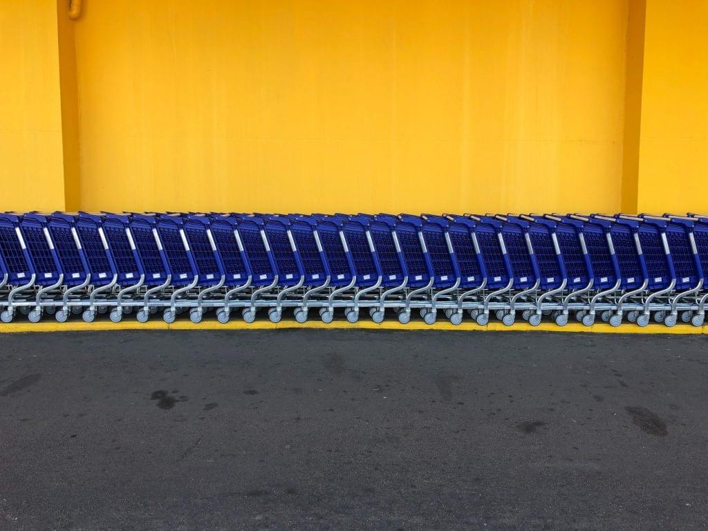 Walmart blue carts against a yellow wall