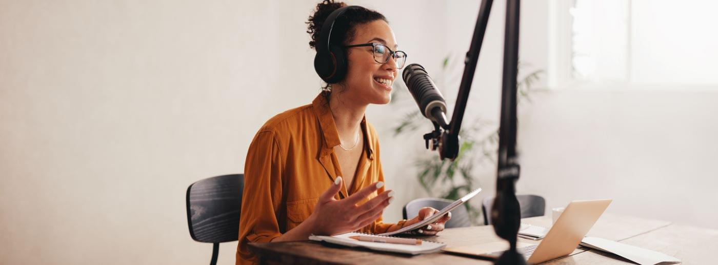 Woman sitting in front of a podcasting microphone for an internal podcast.