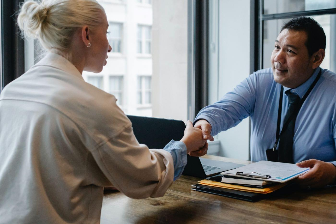 Two people shaking hands celebrating their business partnership.