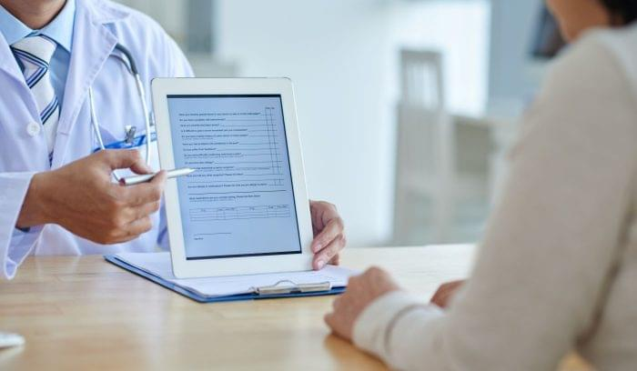 Doctor providing a patient with a questionnaire on a tablet.